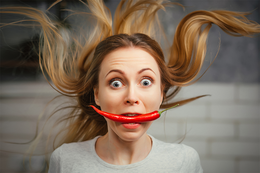 A girl is all red, biting a chilli.