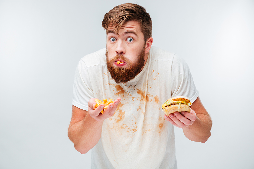 A man, a messy eater, eats a burger and a handful of chips.